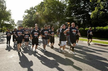 Athlete Thomas Smith ,of Laurel, and Laurel Police Sgt. Erik Lynn carry the torch during the final leg of the 2012 Torch Run Relay June 8, 2012, in Towson.