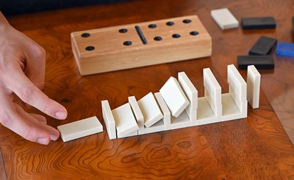 """Chase Blanchette demonstrates a """"slow-stone"""" domino topple. Scott Suko has organized the domino toppling event at Maryland Science Center for years. Chase Blanchette is taking over the duties this year."""