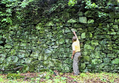 Joe Gochar touches part of a historic mill located on a property in Catonsville that he has worked to preserve as open space.
