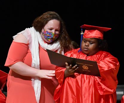 John Archer School graduate Alexis Foreman takes a quick moment to make sure all the details are correct on her diploma as she corwsses the stage with help from teacher Brittany Kleber, left, during the school's graduation ceremony Friday June 4, 2021 at the Amoss Center in Bel AIr.