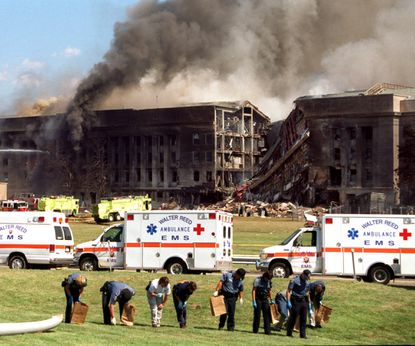 FBI personnel, walking slowly in a row, holding paper collection bags, search for evidence outside the Pentagon on Sept. 11, 2001, near a large gash where the plane hit.
