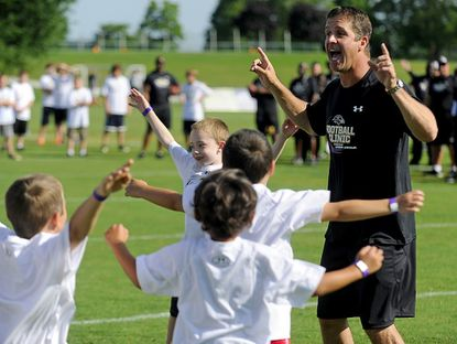 Baltimore Ravens head coach John Harbaugh runs an excercise with youths during the Ravens Football Camp at McDaniel College in Westminster Saturday.