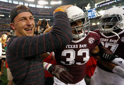 Cleveland Browns quarterback and former Texas A&M Aggies quarterback Johnny Manziel celebrates with Shaan Washington of the Texas A&M Aggies.