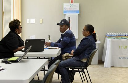Crystal Shivers-Lester, left, a navigator for Seedco, talks with Cyril and Bernadette Johnson of Edgewood at an informational event about options for health coverage on the Maryland Health Exchange, which was held at the Abingdon branch of the Harford county public library.