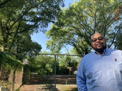 """Matthew King, president of the Harlem Park Community Development Corp., stands in one of the 29 """"inner block parks"""" created 60 years ago as part of an urban renewal plan for the area. This park included a tennis court."""