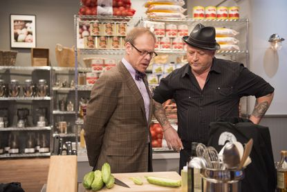 """Mentor Alton Brown checking in on Finalist Rodney Henry cooking for the Mentor's Challenge """"Mystery Bag"""" as seen on Food Network Star, Season 9."""