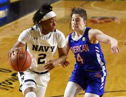 Navy junior Jennifer Coleman, pictured driving past American's Emily Fisher on Jan. 16, has been named second team All-Patriot League after averaging 17.1 points and 11.3 rebounds per game.