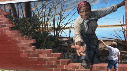 Michael Rosato applies a protective coating to his mural of Harriet Tubman, on an outside wall of the Harriet Tubman Museum & Educational Center in Cambridge.