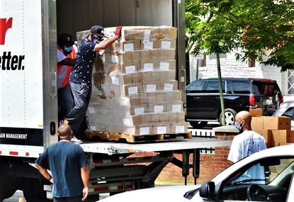 Volunteers with We Our Us, an anti-violence men's movement in Baltimore, unload packages of food for distribution to people in need during the coronavirus pandemic. The group gives away food from refrigerated trailers each week.