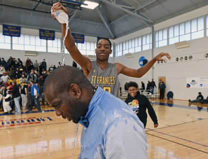 St. Frances' Detwan Montague pours water on coach Nick Myles after the Panthers defeated Mount Saint Joseph, 52-50, to win the Baltimore Catholic League basketball final Sunday at Goucher College.