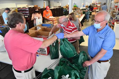 Stu Dettelbach, left, president of Weekend Backpacks, hands a bag of nonperishable food to Alan Taylor, director of operations, at the warehouse where volunteers pack the bags of food to help sustain homeless Baltimore City schoolchildren and their families on weekends. The nonprofit has increased donations to respond to greater food insecurity during the pandemic. July 5, 2020
