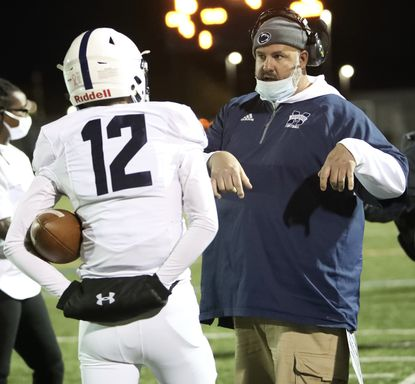 Marriotts Ridge has hired TJ Welsh as its new head football coach. Welsh, pictured here talking to quarterback Casey Pung during a game this past season, is being promoted from his post as the team's offensive coordinator.