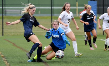 From left, Erin Marciszewski, Perry Hall forward, is stopped by getting a shot off in the first half by Harford Tech goalkeeper Raegan Salamone at the Bobcat Cup at Bel Air High School.