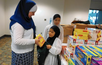 "Malika MacDonald, the national director of transitional housing network for ICNA Relief USA, one of the nation's largest domestic Muslim charities, gets some help from her granddaughter, Amira Bey, 8, at the Baltimore Convention Center as they prepare to fill ""blessing bags."""
