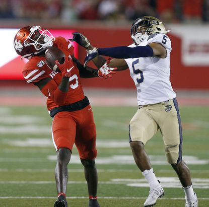 HOUSTON, TEXAS - NOVEMBER 30: Marquez Stevenson #5 of the Houston Cougars makes a one handed catch as Michael McMorris #5 of the Navy Midshipmen defends during the first half on November 30, 2019 in Houston, Texas. (Photo by Bob Levey/Getty Images) ** OUTS - ELSENT, FPG, CM - OUTS * NM, PH, VA if sourced by CT, LA or MoD **