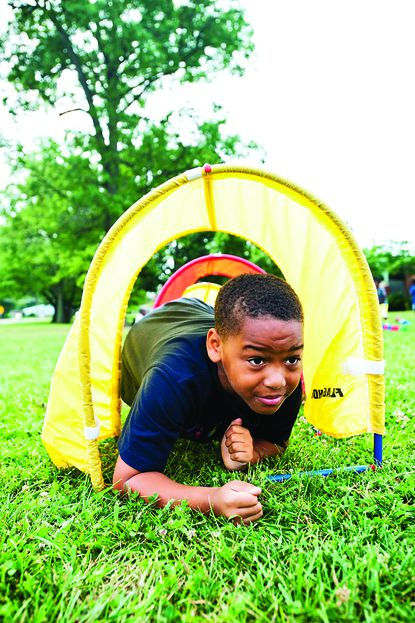 Aaron Davis, 8, crawls through an obstacle course at Baltimore County's free Police Athletic League summer camp.