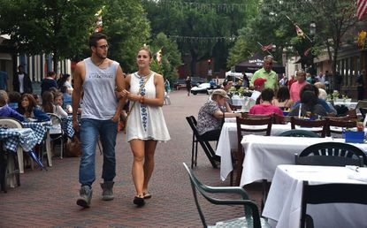 Eric Arcadia, of Fort Washington, and Alli Graf, of Annapolis, walk down West Street during the 2019 Inner West Street Association's annual Dining Under the Stars. The city has announced West Street and other city streets will be used as recovery zones, areas where businesses may serve food and drinks and sell their wares in outdoor spaces starting Monday