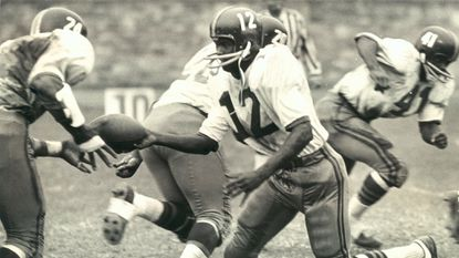 Morgan State quarterback Daryl Johnson hands off to Earl Mayo during a game in 1966.