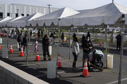 In this Jan. 7, 2021, file photo, people line up at a COVID-19 walk-up testing site on the Martin Luther King Jr. Medical Campus in Los Angeles. (AP Photo/Marcio Jose Sanchez, File)