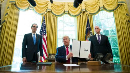 FILE - In this June 24, 2019, file photo, President Donald Trump holds up a signed executive order to increase sanctions on Iran, in the Oval Office of the White House in Washington, with Treasury Secretary Steven Mnuchin, left, and Vice President Mike Pence.