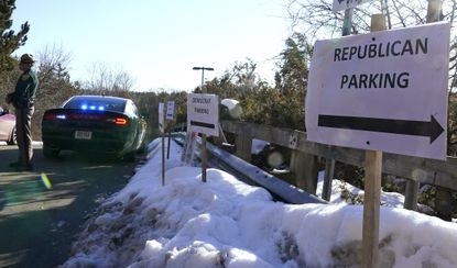 """A sign directs Republican and """"Democrat"""" legislators to their parking areas at a New Hampshire House of Representatives session held at NH Sportsplex, due to COVID-19, in Bedford, N.H., on Feb. 24, 2021. Republicans, including the lawyers who defended former President Donald Trump during the second impeachment trial, routinely drop the """"i-c"""" when referring to the Democratic Party or its policies."""