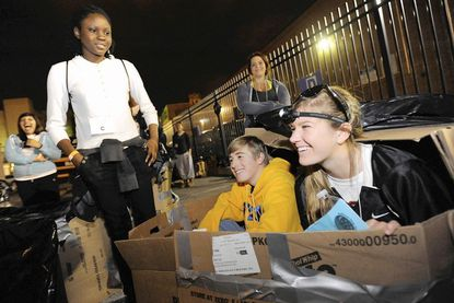 Loyola Blakefield senior Mitchell Hopkins, left, in box, and Megan Woods, a McDonogh senior, right, check out a cardboard shelter they constructed while Chesapeake High School senior Hannah Adesuyi, left, and Mercy High School senior Jillian Phelps, back right, look on during the Baltimore Sleep Out for the Homeless event at Our Daily Bread Employment Center in Baltimore on Oct. 28.