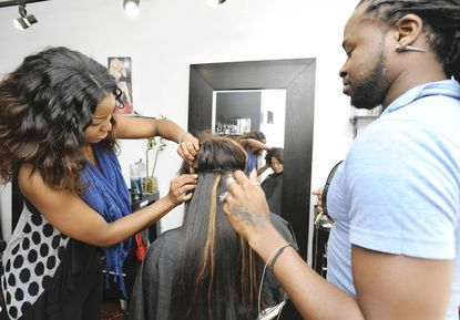 """Reginald """"Reggie"""" Dowdy, right, is artistic director of Geometrics Hair Studio on O'Donnell St. April McGill-Willhide, left, assists him in wefting hair extensions into Shaina Bloom's hair."""