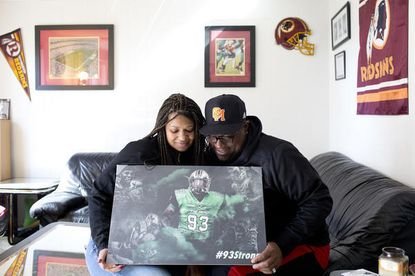 Melissa Aaron and her husband Larry pose for a photo in their home with a photo of their late son in Columbia on Friday, March 23, 2018.