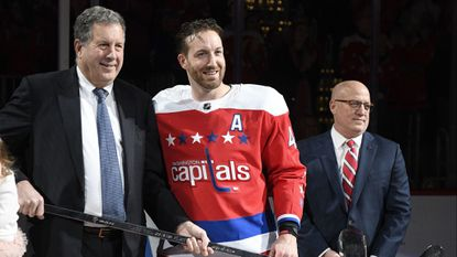 Capitals defenseman Brooks Orpik, center, poses with Dick Patrick, left, team president, and Bill Daly, deputy NHL commissioner, after he was given a silver stick during a ceremony to honor Opik for playing 1,000 NHL hockey games.