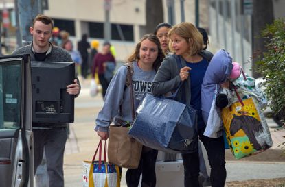 Towson University student Gracie Goetz (center) of Bel Air, moves out of her dorm with help from her mother Jeanette after it was announced that classes were cancelled for the rest of the week as a precautionary measure due to Covid-19 virus.
