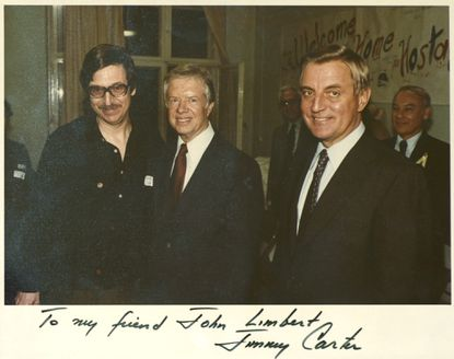 Ambassador John W. Limbert, Jr. (left) is pictured on a photo displayed on his office wall with former U.S. President Jimmy Carter (center) and former V.P. Walter Mondale (right). On Limbert's walls are many mementos of his experience as one of the Iranian hostages 26 years ago. He now teaches political science at the Academy. . -- THE BALTIMORE SUN STAFF -- 0024 MANDATORY CREDIT: No Mags, No Sales, No Internet, No TV, Washington Post, Washington Times, Baltimore Examiner and Washington Examiner OUT