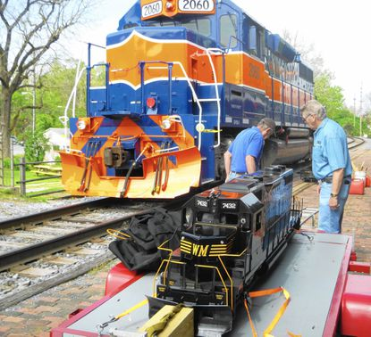 Glenn Sharpe, left, and Bob Parks unload a miniature diesel engine train from the Chesapeake & Allegheny Steam Preservation Society at the 2014 National Train Day festivities hosted by the Western Maryland Railway Historical Society Museum.