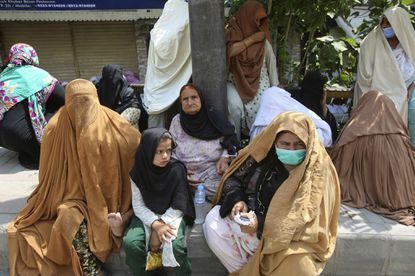Women wait their turn outside a bank to receive cash under a government program for families in need during a nationwide lockdown to try to contain the outbreak of the coronavirus, in Peshawar, Pakistan, on June 29, 2020.