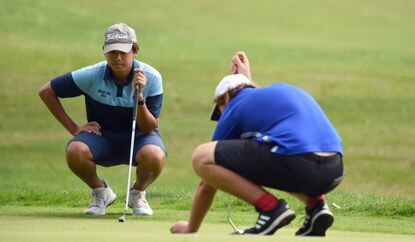 River Hill's Benjamin Siriboury eyes the break on the 13th green as he waits for playing partner, Centennial's Dustin Stocksdale, to line up a putt during the District V Championship golf tournament at Hobbit's Glen Golf Course in Columbia on Monday, Oct. 4, 2021.