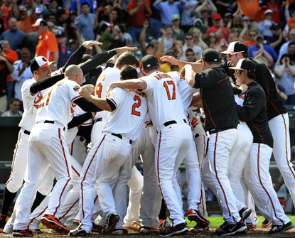 Wilson Betemit is mobbed by his Orioles teammates after his walk-off homer gave them a 5-2 win over the A's.