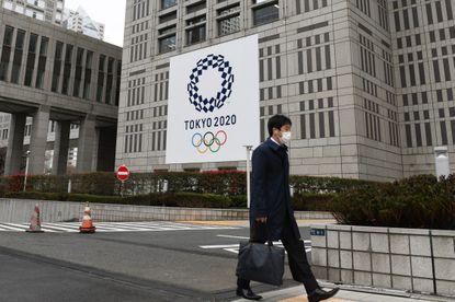 A man wearing protective mask walks past banners of the upcoming Tokyo 2020 Olympic and Paralympic Games outside the Tokyo Metropolitan Government building in Tokyo, Monday, March 23, 2020. The Summer Olympics in Tokyo will be postponed a year until 2021 because of the coronavirus pandemic.