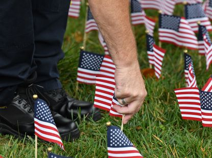 Jim Plumer, a member of the Bel AIr Volunteer Fire Company and Harford County Sheriff's deputy joins town employees, commissioners and others as they place over 2000 flags around Bel Air Town Hall Thursday, September 9, 2021 to honor those lost on September 11, 2001. .