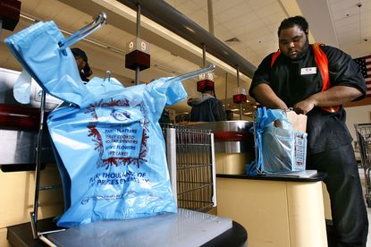 An employee bags groceries at a Giant supermarket. The Baltimore City Council is considering banning the use of such plastic bags.