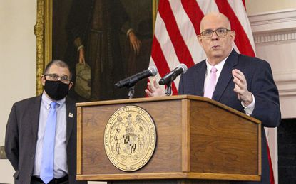 Gov. Larry Hogan is flanked by Dennis R. Schrader, the state's acting health secretary, as he addresses developments in the coronavirus pandemic in Maryland.