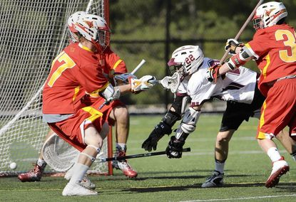 Despite the effort of Calvert Hall defenders Kelton Black, left front, and Garrett Epple, right, Boys' Latin attackman Colin Chell sends the ball past goalie Dimiitri Pecunes to pull the Lakers to within a goal of the Cardinals late in the first half. However, Calvert Hall went on a 7-0 run to secure a 12-5 victory on Tuesday afternoon.