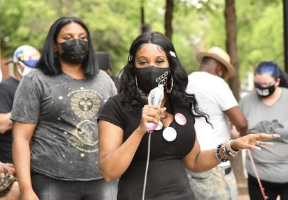 Marah OÕNeal, left, listens to Tawanda Jones speak outside the Forensic Medical Center on W. Baltimore St., as she urges those at the rally to push for new investigations of the cases overseen by former medical examiner David Fowler. Jones wants a fresh investigation on the cause of death for her brother, Tyrone West. April 28, 2021