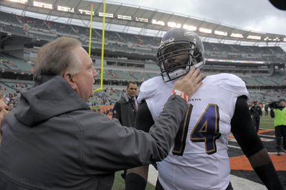 Ravens right rackle Michael Oher talks with his adoptive father, Sean Tuohy, before the game against the Cincinnati Bengals.