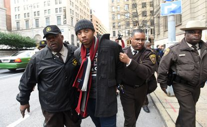Officers from the Baltimore Sheriff's Department arrest activist Kwame Rose in front of Courthouse East after the deliberations ended in a hung jury in the trial of Officer William Porter.