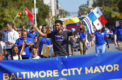 Baltimore City Mayor Brandon Scott walks in the Fiesta Baltimore parade.