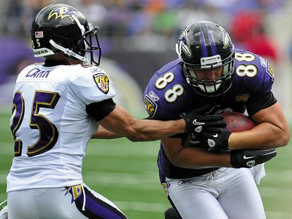 Ravens tight end Dennis Pitta fights past corner back Chris Carr during practice at M&T Bank Stadium in Baltimore.