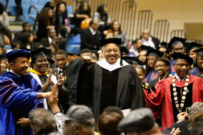 Morgan State University Board of Regents Chairman Kweisi Mfume, left, the Rev. Jesse Jackson, center, and and university President David Wilson joke with the crowd before Jackson spoke at the school's December commencement on Friday.