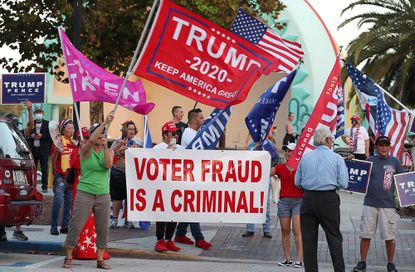 """Supporters of President Donald Trump wave flags and chant """"Stop the Cheat!"""" as they gather to rally at Lake Eola Park in Orlando, Florida, on Thursday, Nov. 5, 2020. The supporters were rallying against what they perceive as election fraud in Tuesday's presidential election."""