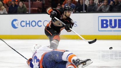 Ducks forward Andrew Cogliano puts a shot on net under pressure from Islanders defenseman Travis Hamonic during the second period of a game on Nov. 22.