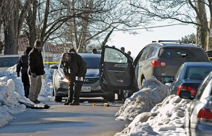 Baltimore Police officers investigate the scene at 3400 block of Piedmont Avenue where a driver was shot by police officers as he backed his SUV into an unmarked police vehicle and injured one of the officers.