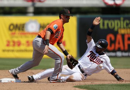 Orioles second baseman Paul Janish reaches down for the throw as Minnesota Twins' Eddie Rosario steals the bag with Eduardo Escobar at bat in the fifth inning of a spring training game, Sunday, March 13, 2016, in Fort Myers , Fla.